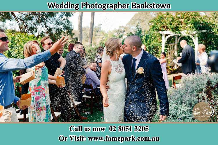 Photo of the Bride and the Groom kissing while showering rice by the visitors Bankstown NSW 2200