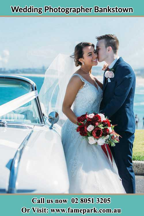 Photo of the Groom kiss the Bride besides the bridal car Bankstown NSW 2200