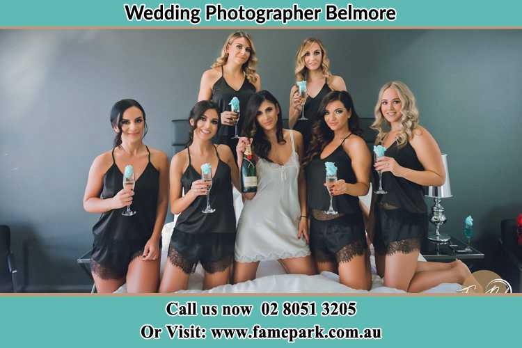 Photo of the Bride and the bridesmaids wearing lingerie and holding glass of wine on bed Belmore NSW 2192