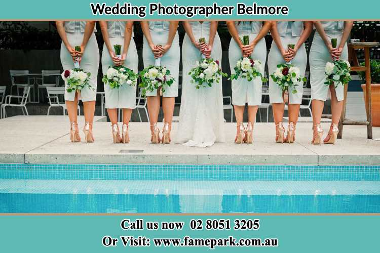 Behind photo of the Bride and the bridesmaids holding flowers near the pool Belmore NSW 2192