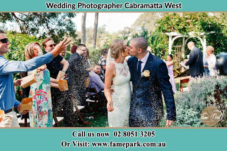 Photo of the Bride and the Groom kissing while showering rice by the visitors Cabramatta West NSW 2166