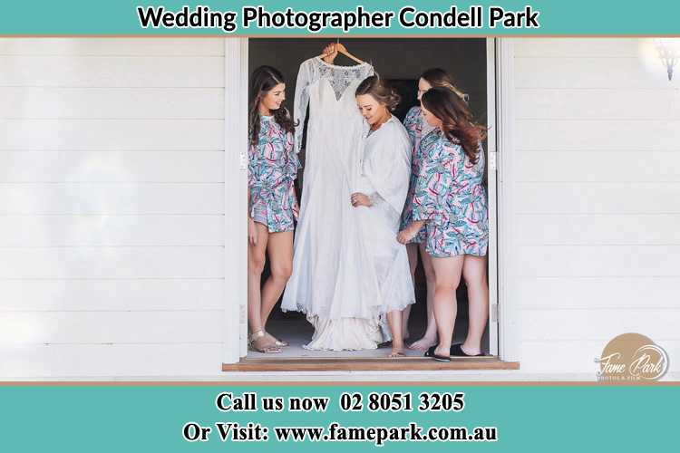 Photo of the Bride and the bridesmaids checking the wedding gown at the door Condell Park NSW 2200