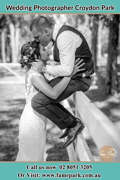 Photo of the Groom sitting on the fence while kissing the Bride on the forehead Croydon Park NSW 2133