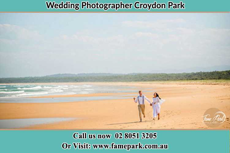 Photo of the Groom and the Bride walking at the sea shore Croydon Park NSW 2133