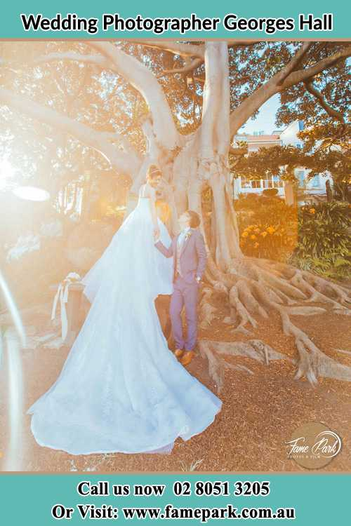 Photo of the Bride and the Groom looking each other besides the tree Georges Hall NSW 2198