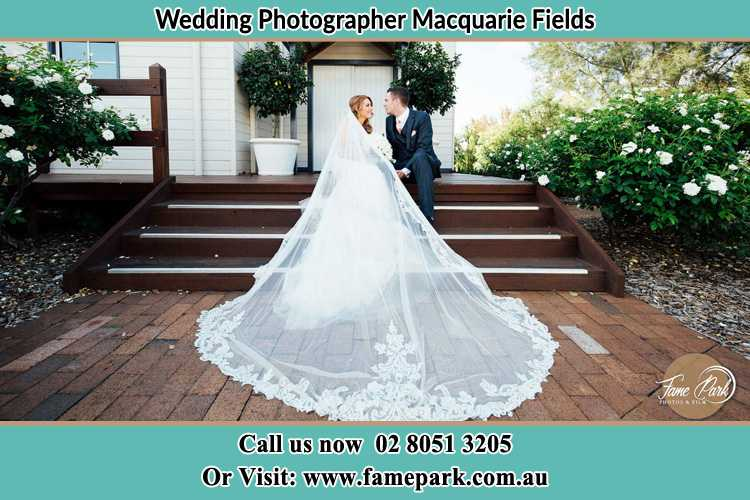 Photo of the Bride and the Groom looking each other while sitting at the staircase Macquarie Fields NSW 2564