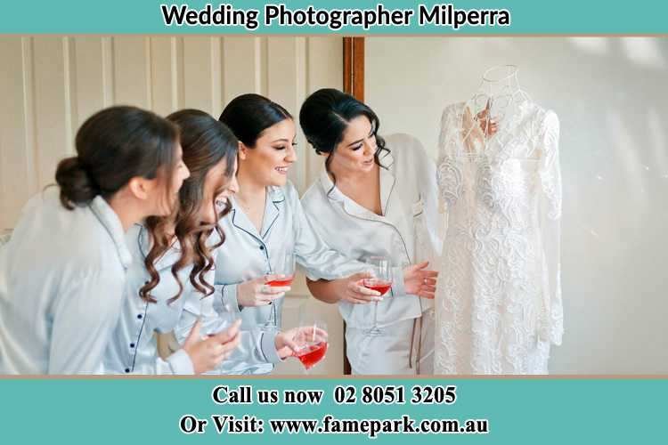 Photo of the Bride and the bridesmaids looking at the wedding gown Milperra NSW 2214