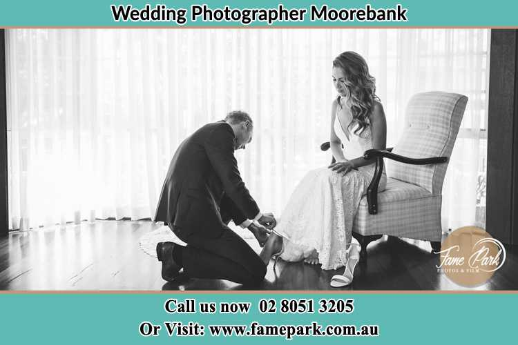 The Bride is being helped by the Groom trying to put on her shoes Moorebank NSW 2170