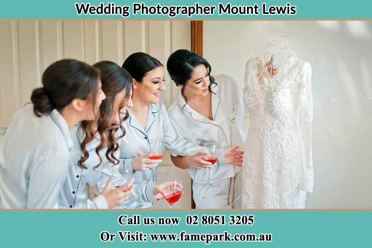 Photo of the Bride and the bridesmaids looking at the wedding gown Mount Lewis NSW 2190