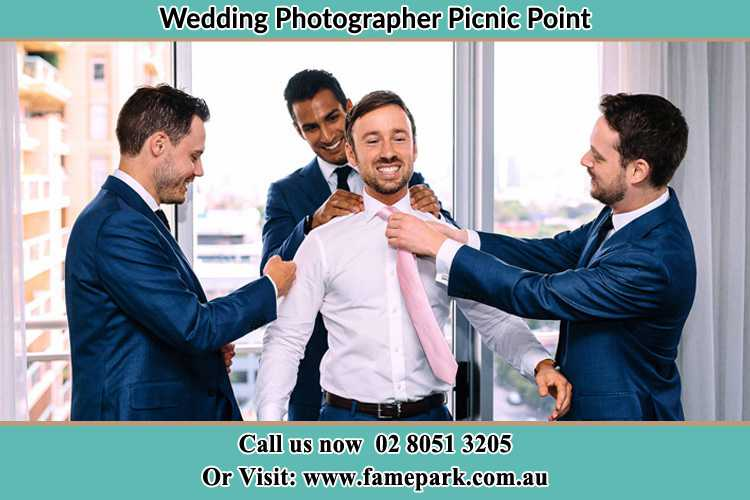 Photo of the Groom helping by the groomsmen getting ready Picnic Point NSW 2213