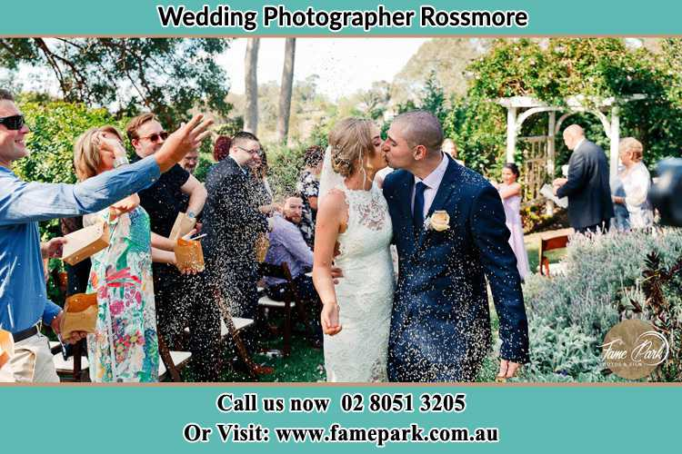 Photo of the Bride and the Groom kissing while showering rice by the visitors Rossmore NSW 2557