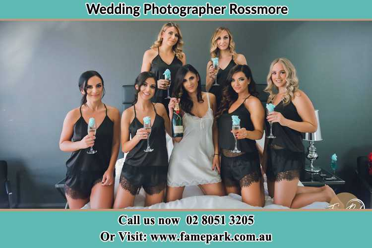 Photo of the Bride and the bridesmaids wearing lingerie and holding glass of wine on bed Rossmore NSW 2557