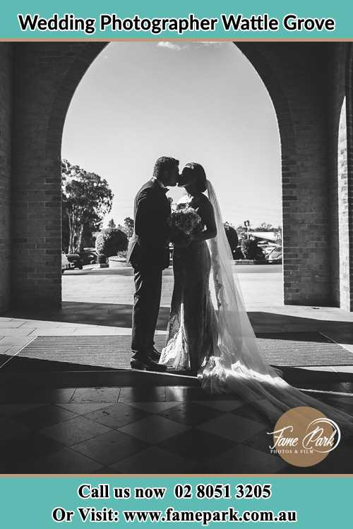 Photo of the Groom and the Bride kissing at the front of the church Wattle Grove NSW 2713