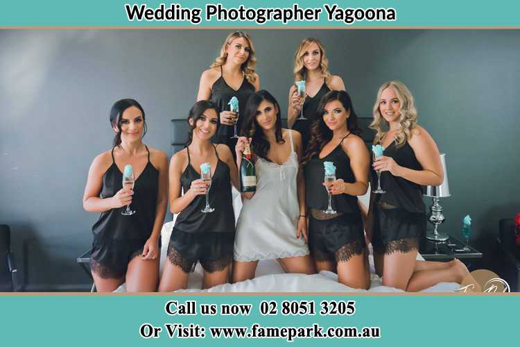 Photo of the Bride and the bridesmaids wearing lingerie and holding glass of wine on bed Yagoona NSW 2199